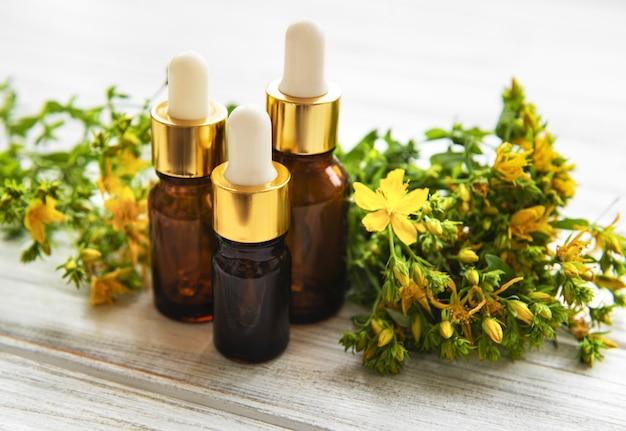 Botellas con extracto de hierba de san juan en la mesa de madera Foto Premium