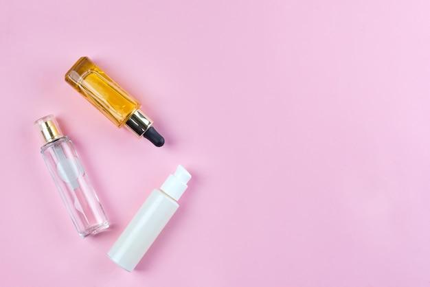 Botellas y frascos con cosméticos naturales para el cuidado de la piel, cremas y aceites sobre fondo rosa. Foto Premium