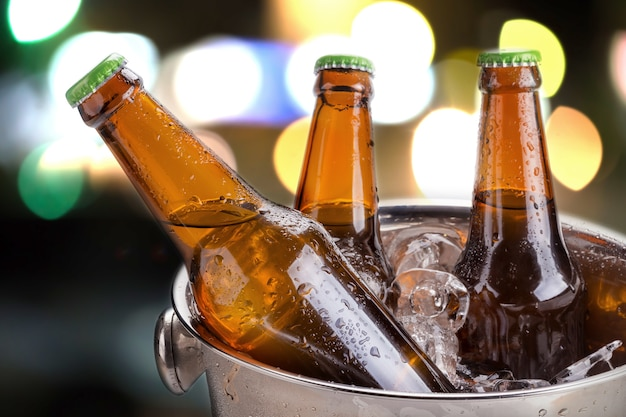 Botellas frías de cerveza en cubo con hielo sobre fondo blanco Foto Premium