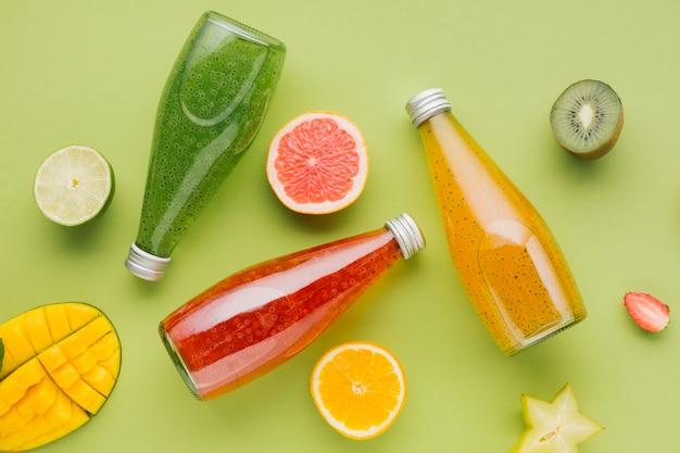 Botellas de jugo de colores y rodajas de fruta Foto gratis