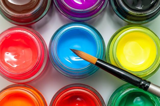 Botellas multicolores poster color y pincel sobre un fondo blanco pinturas aisladas en contenedores vista superior copyspace Foto Premium