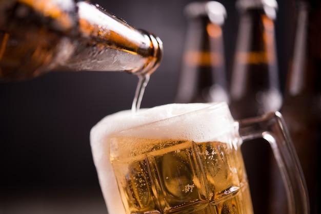 Botellas de vidrio de cerveza con vidrio y hielo sobre fondo oscuro Foto gratis