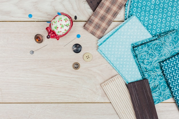 Botones; cojín de fieltro hecho a mano y tela doblada azul en el escritorio de madera Foto gratis