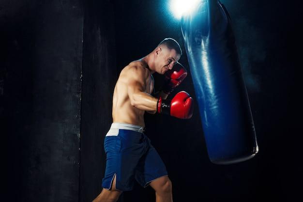 Boxeador masculino en saco de boxeo con espectacular iluminación vanguardista Foto gratis
