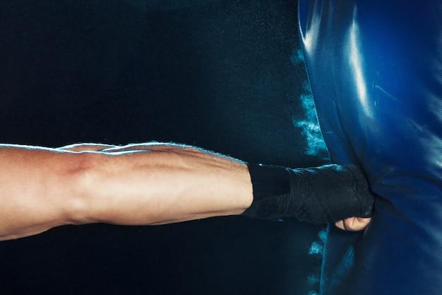 Boxeador masculino en saco de boxeo Foto gratis