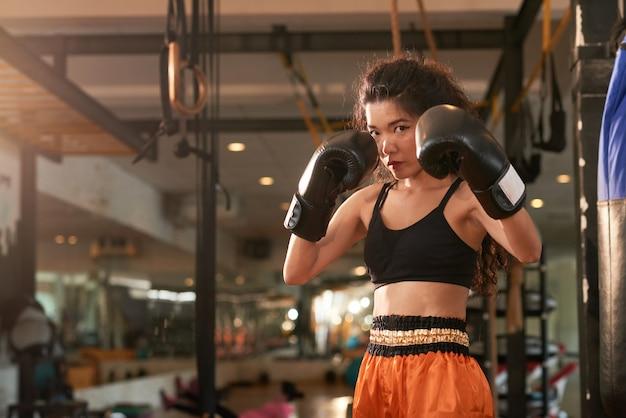 Boxeador de muay thai mirando a la cámara listo para dar un golpe Foto gratis