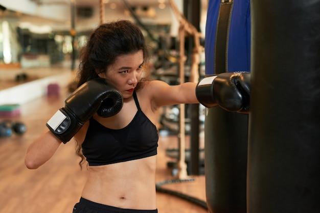 Boxeadora de muay thai entrenando con pelota de boxeo Foto gratis