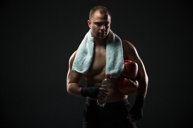 Boxer descansando con agua y una toalla después del entrenamiento Foto gratis