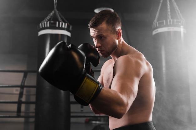 Boxer con guantes negros de entrenamiento Foto gratis