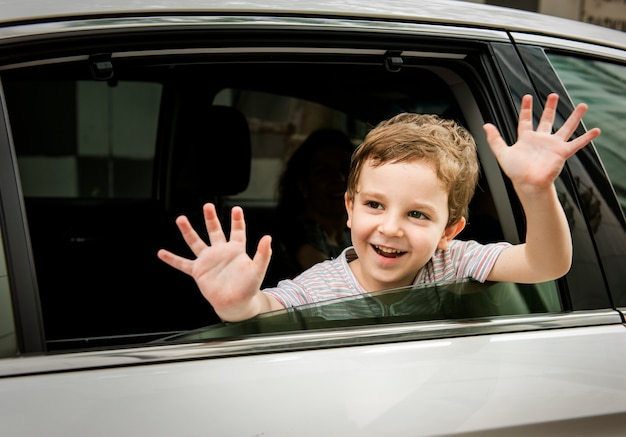 Boy child in car alegre sonriendo saludo Foto gratis