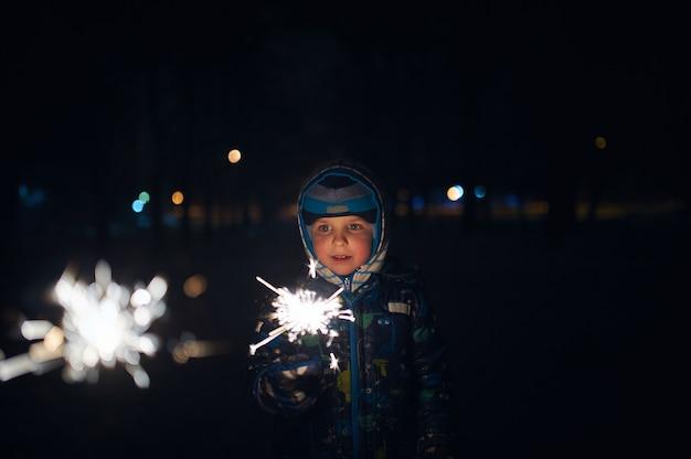 Boy sostiene una bengala en sus manos mientras celebra un año nuevo en la calle por la noche. Foto Premium