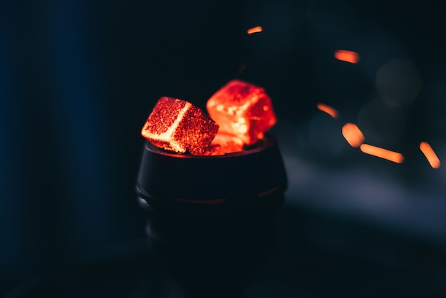 Brasas rojas para la cachimba con chispas sobre fondo oscuro Foto Premium