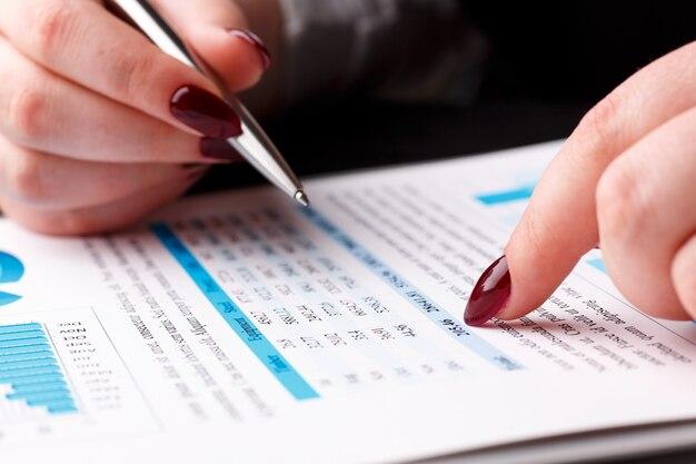 Brazo femenino sostenga y señale la pluma de plata en gráfico financiero Foto Premium