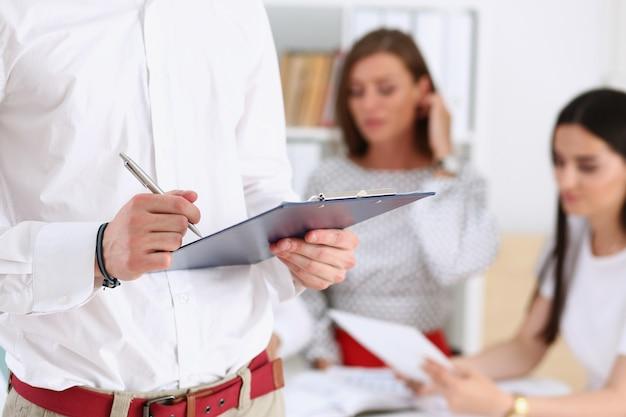 Brazo masculino en la lectura de la oficina y la firma del contrato de trabajo en el portapapeles con pluma de plata closeup golpear una decisión de negociación motivación de cuello blanco concepto de agente de seguros de venta corporativa Foto Premium
