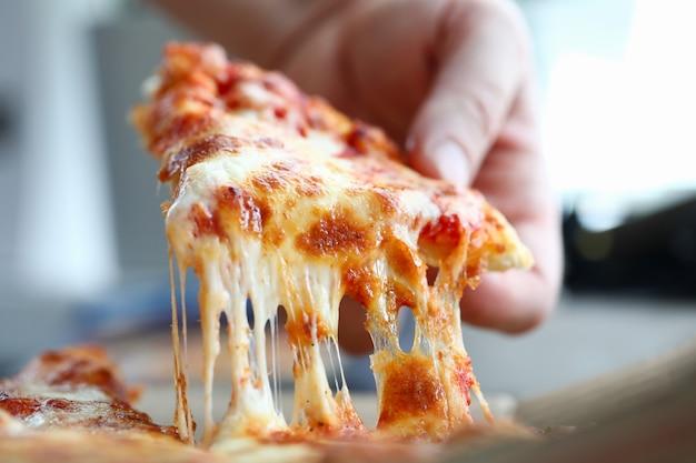 Brazo masculino tomando una rebanada de pizza fresca sabrosa con queso Foto Premium