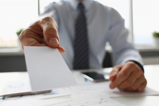 Brazo masculino en traje dar tarjeta de visita en blanco al visitante Foto Premium