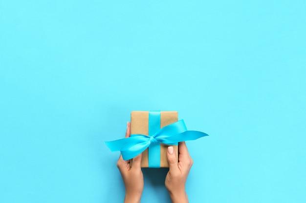 Brazos de mujer con caja de regalo con cinta azul en color, vista superior Foto Premium