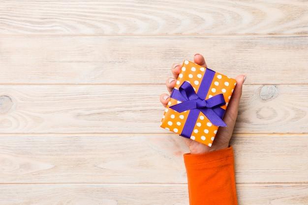 Brazos de mujer con caja de regalo con cinta de color en la mesa de madera rústica amarilla, vista superior Foto Premium