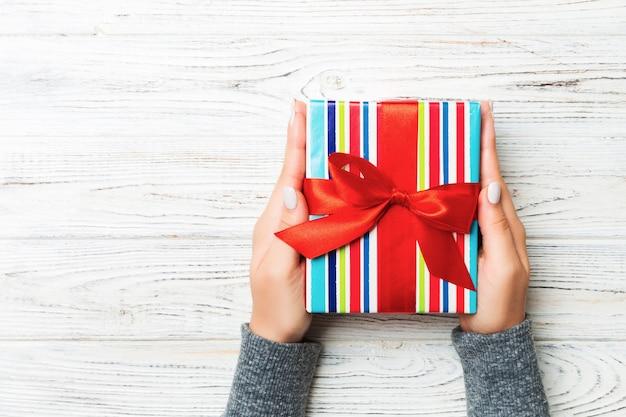 Brazos de mujer con caja de regalo con cinta de color en la mesa de madera rústica blanca, vista superior y para usted diseño Foto Premium
