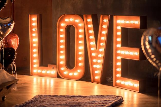 La brillante palabra amor en un interior. cartas enormes cuestan amor de bombillas en un piso Foto Premium