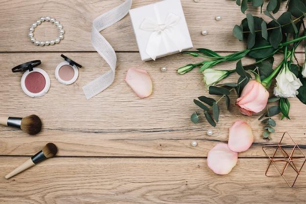 Brocha de maquillaje; polvos faciales compactos; perlas caja de regalo; rosa y flores de eustoma en escritorio de madera. Foto gratis
