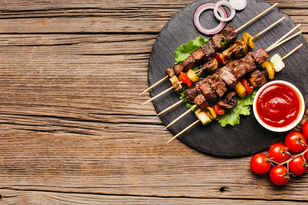 Brochetas de barbacoa con carne y verdura sobre pizarra circular negra Foto gratis