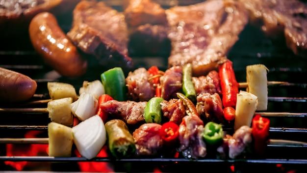 Brochetas de barbacoa a la parrilla brochetas con verduras a la parrilla en llamas Foto Premium