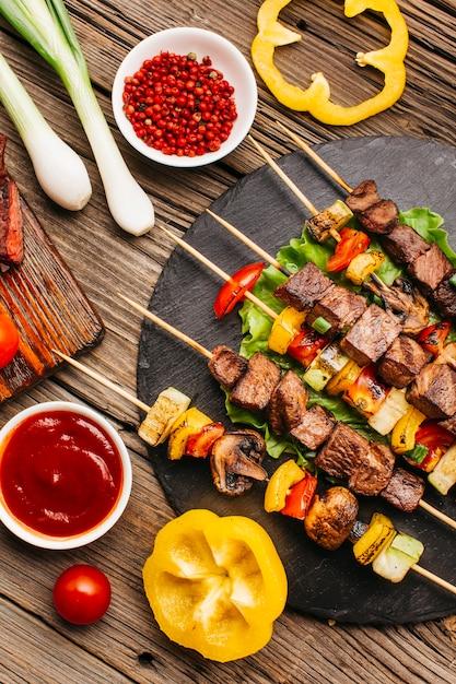 Brochetas de carne a la parrilla con vegetales en mesa de madera Foto gratis