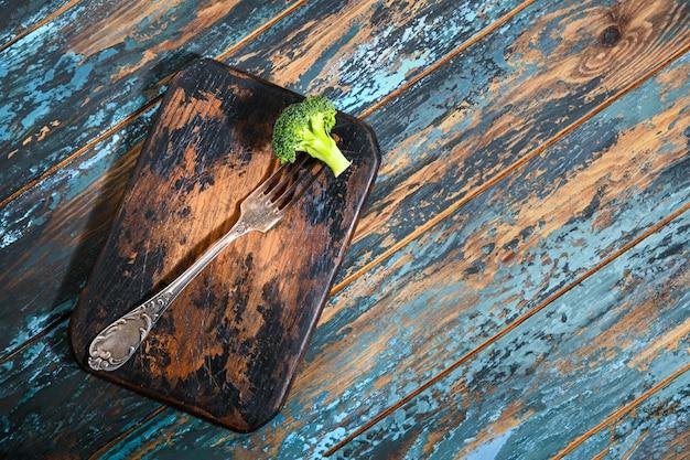 Brócoli en tenedor antiguo sobre tablero de cocina quemado en mesa azul de madera teñida en bruto. Foto Premium