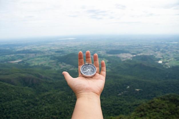 Brújula mano con vista del bosque, senderismo y perdido en el concepto de bosque. enfoque suave, Foto Premium