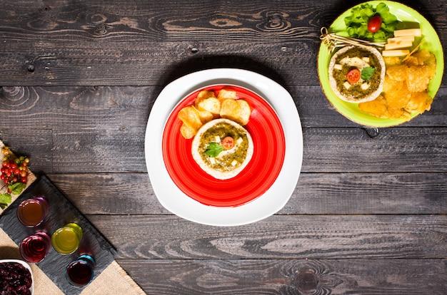Bruschetta sabroso y delicioso con chips de hierbas de queso de aguacate tomates y licor sobre un fondo de madera. Foto Premium