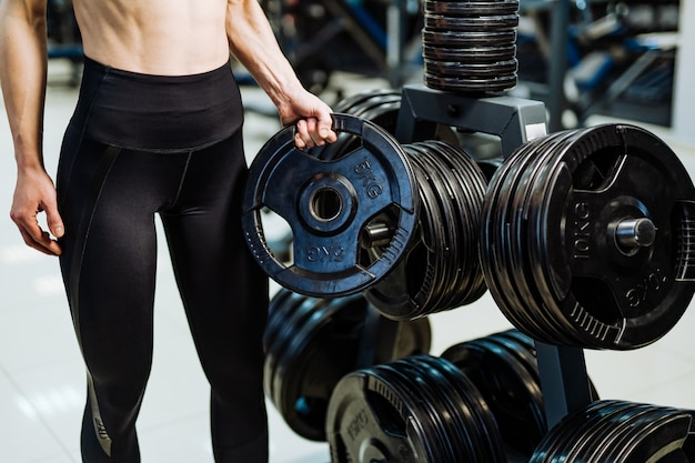 Brutal mujer atlética bombeando musculatura con pesas Foto Premium