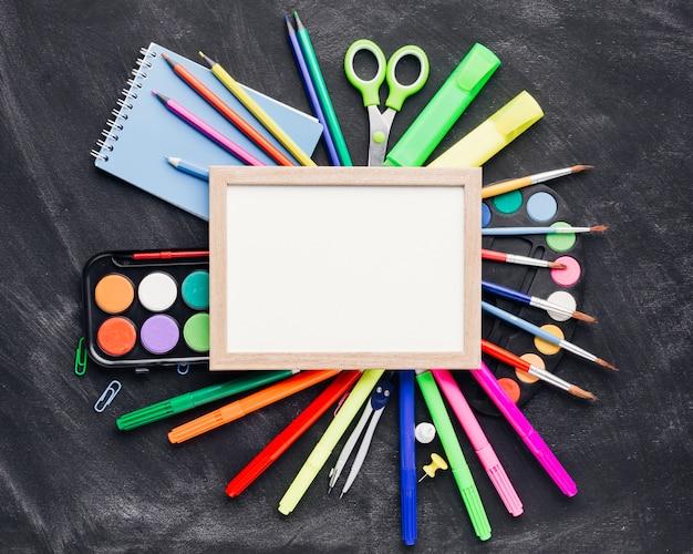 Btight papelería y acuarela alrededor de marco en blanco Foto gratis