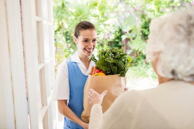 Buena enfermera llevando verduras a un paciente viejo en casa Foto Premium