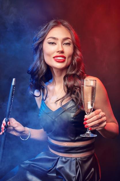 Buena mujer fumando shisha y bebiendo cócteles en un bar Foto Premium