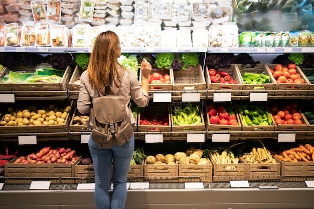 Buena mujer de pie delante de los estantes de verduras eligiendo qué comprar Foto gratis
