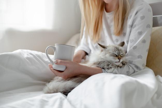 Buenos días concepto chica rubia con el gato y la taza de café hygge Foto Premium