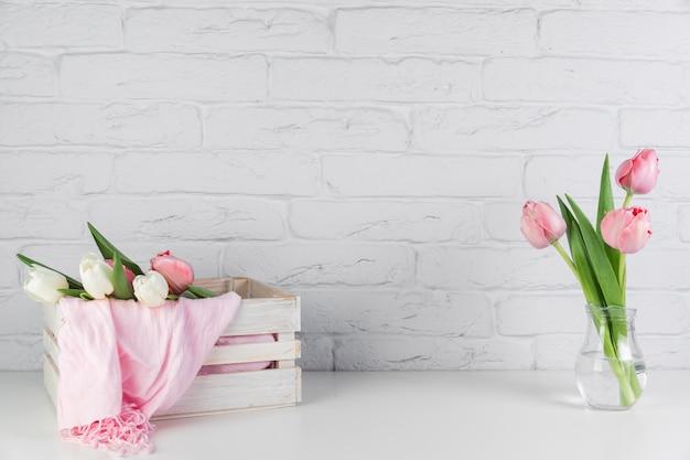 Bufanda rosada dentro de la bufanda de madera y jarrón de tulipanes en el escritorio contra la pared de ladrillo blanco Foto gratis