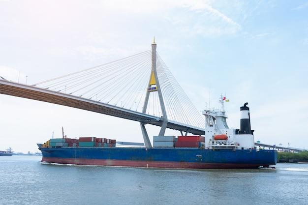 Buque de carga que transporta contenedores y corre bajo el puente para la exportación de mercancías. Foto Premium