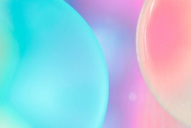 Burbujas de oxígeno en el agua en un fondo azul y rosa Foto gratis