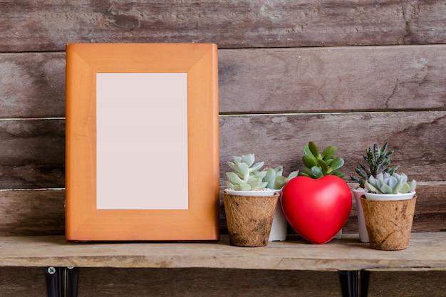 Burlarse de marco de madera en estante con corazón de san valentín y fondo de madera rústico de cactus Foto Premium
