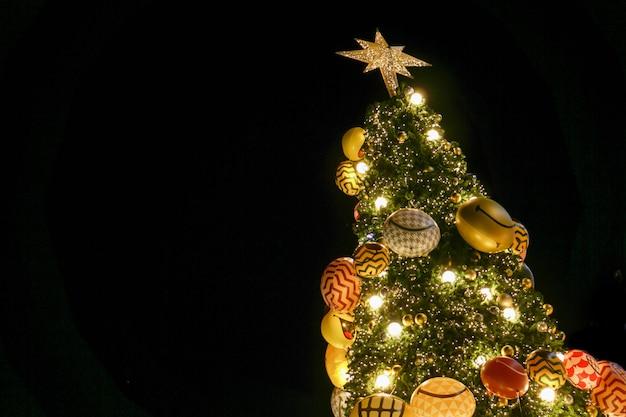 Busque la vista del árbol de navidad y decore con iluminación led aislada en negro. Foto Premium