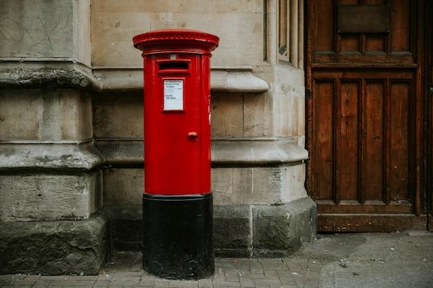 Buzón británico rojo icónico en una ciudad Foto gratis
