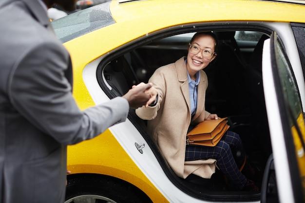 Caballero ayudando a mujer joven a salir de taxi Foto gratis