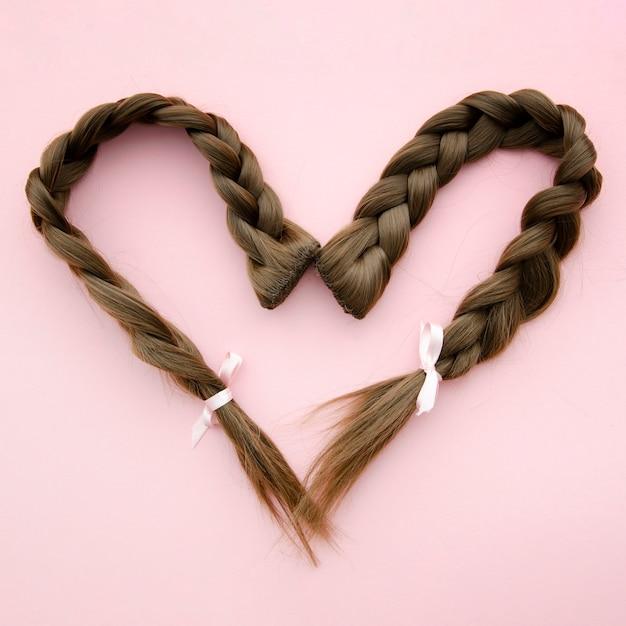 Cabello trenzado en forma de corazón con cinta Foto gratis