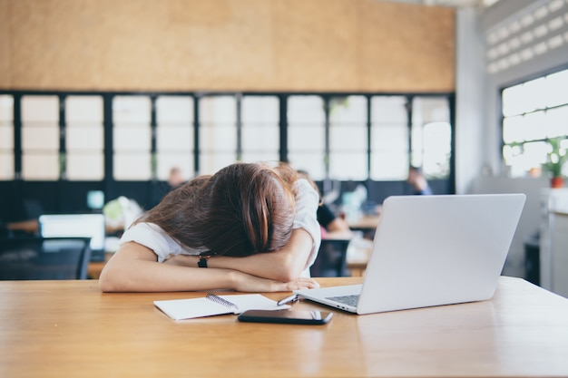 Cabeza agotada frustrada de la mujer abajo en la tabla. finanzas del logro y concepto del negocio Foto Premium