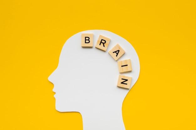 Cabeza blanca con palabra de cerebro de letras scrabbles Foto gratis
