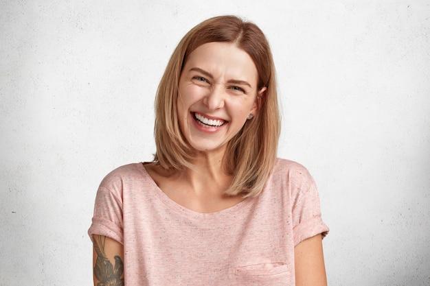 En la cabeza de la modelo femenina contenta y satisfecha frunce el ceño por la risa, está de buen humor mientras escucha una historia divertida de un amigo, se viste informalmente, pasa el tiempo libre en casa. Foto gratis
