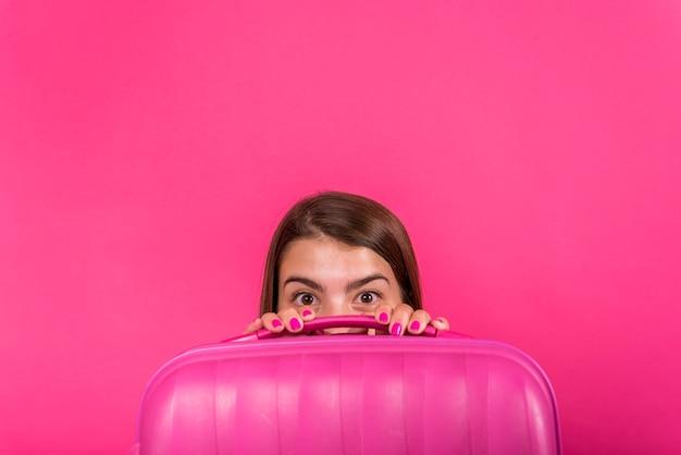 Cabeza de mujer escondida detrás de una maleta rosa Foto gratis
