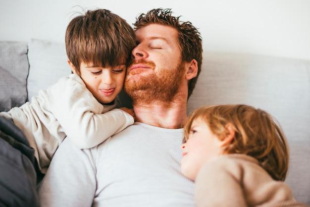 La cabeza de papá se inclina contra el hijo en el sofá Foto gratis